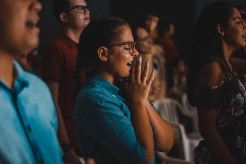 People with eyes closed in audience. Photographer: Luan Cabral | Source: unsplash