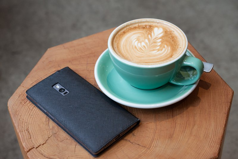 Phone in case and latte on a small coffee table / Photographer: Kim S. Ly   Source: Unsplash