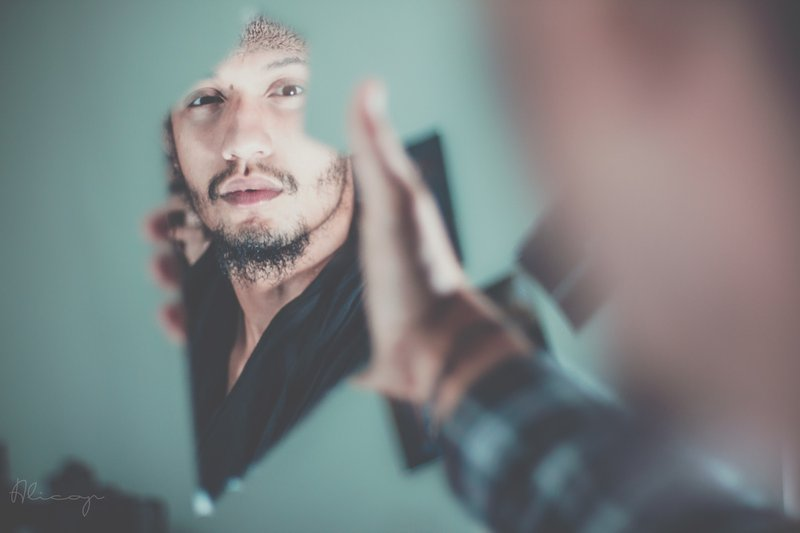 Guy looking at fraction of face through shard of mirror    Photographer: Fares Hamouche   Source: Unsplash