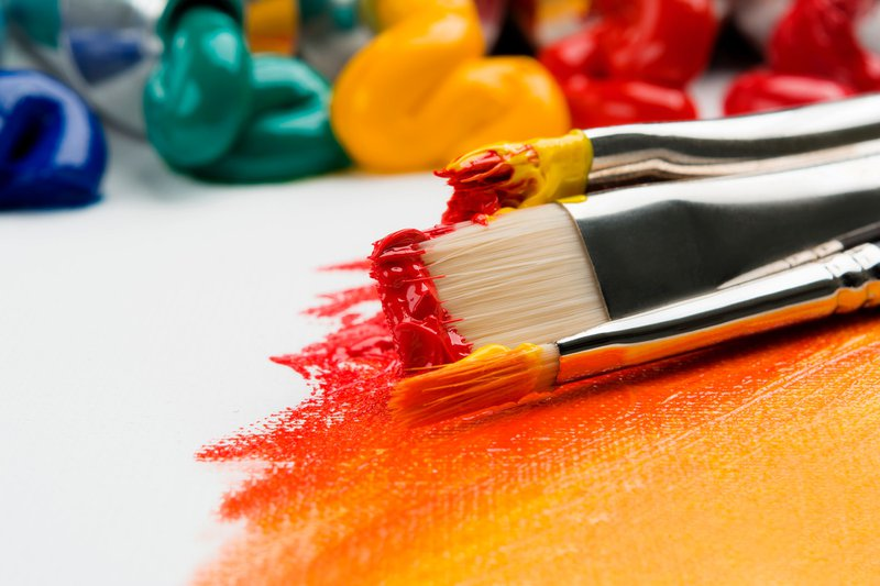 Close up of brushes on a canvas covered in red and yellow paint