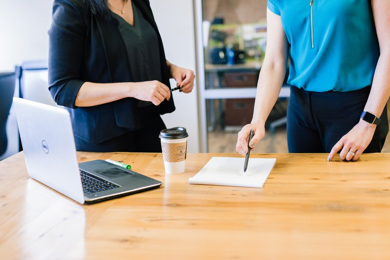Two people standing at a desk with laptop, coffee, pen and paper on desk / Photographer: Amy Hirschi   Source: Unsplash