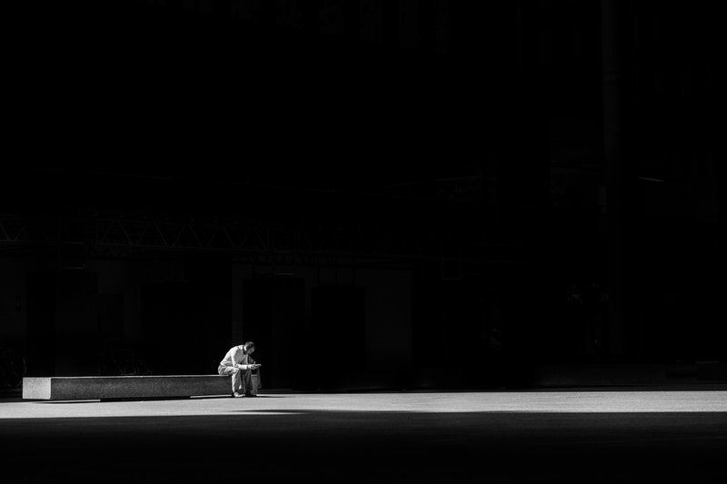black and white of man sitting alone on bench in large empty space // Photographer: Matthew Henry | Source: Unsplash