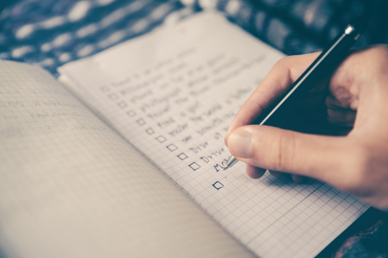 hand holding pen writing checklist in a notebook