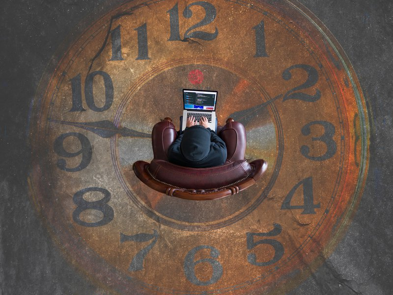 View from above of guy sitting on chair in the middle of  painted clock / Photographer: Kevin Ku   Source: Unsplash