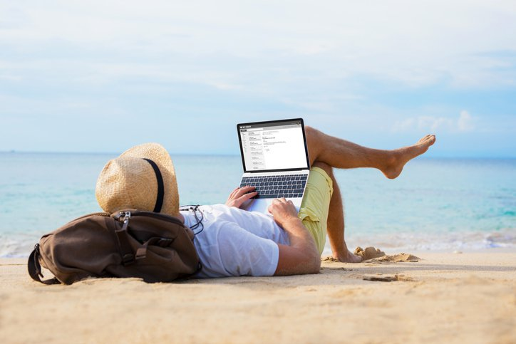 Unrecognizable male reading email on laptop while relaxing on beach