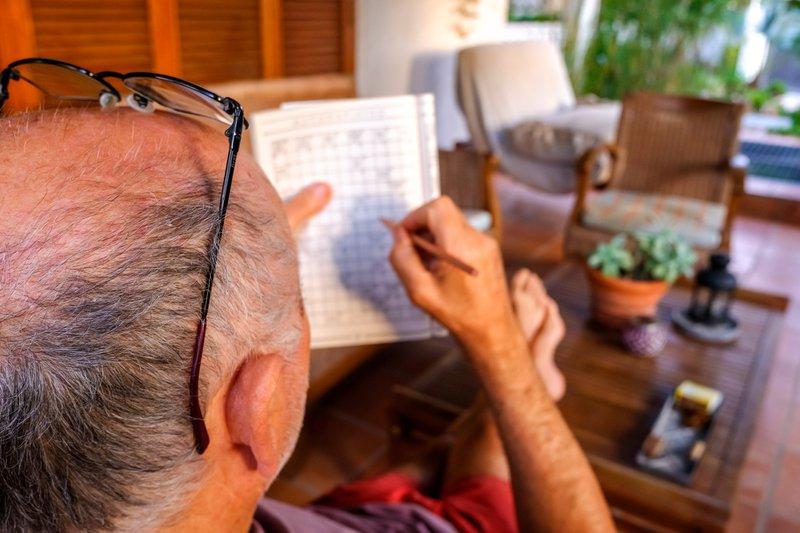 older gentleman completing crossword