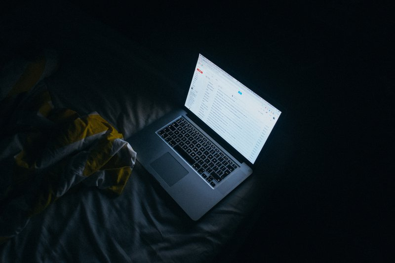 silver laptop on bed in a dark room