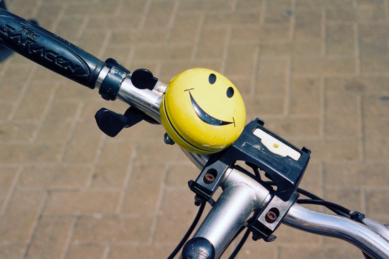 A bicycle bell with a yellow smiling face. Shot on film.