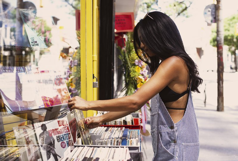 woman going through vinyl records at a music store