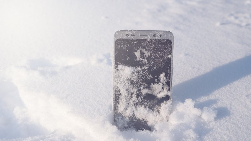 A phone standing upright in the snow, particles of snow covering the screen.