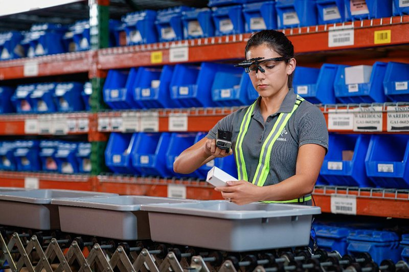 A female worker scans a product using rugged wearables: a ring scanner and smart glasses.