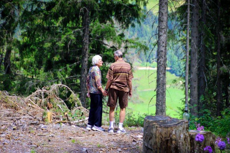 verjaardagscadeau: de natuur in - ouder koppel hand in hand in een bos