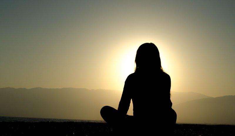 vrouw die zittend naar zonsondergang kijkt