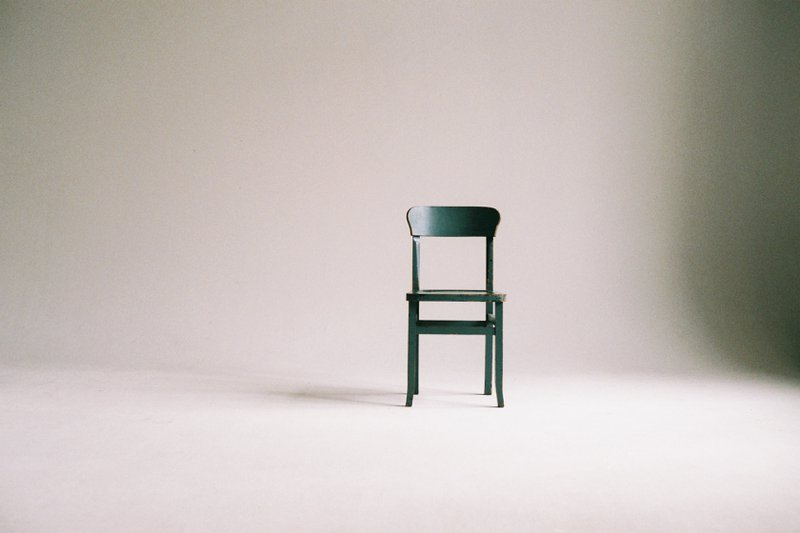 Donkergroene stoel tegen beige muur
