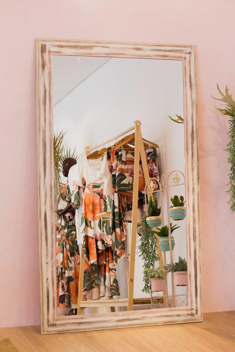 Verticale spiegel met in de weerspiegeling een kledingrek