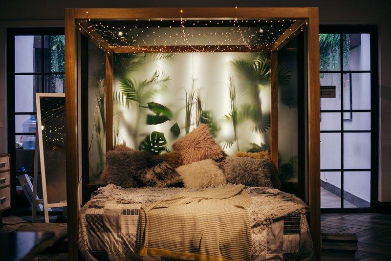 Urban jungle als één van de interieurtrends van 2020: slaapkamer met zachte kussen, planten en houten frame