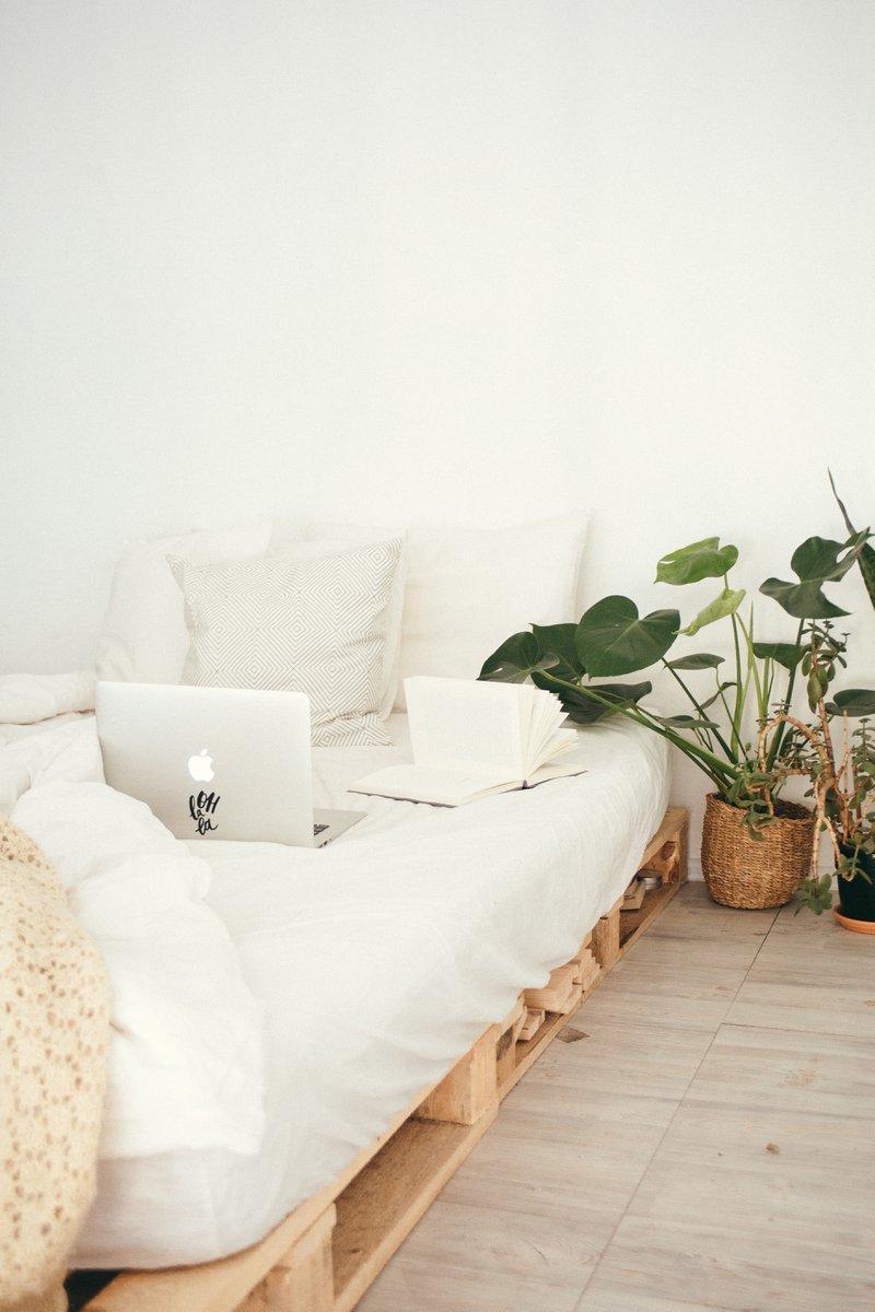 Paletten bed, met witte lakens, een laptop en planten in een mand