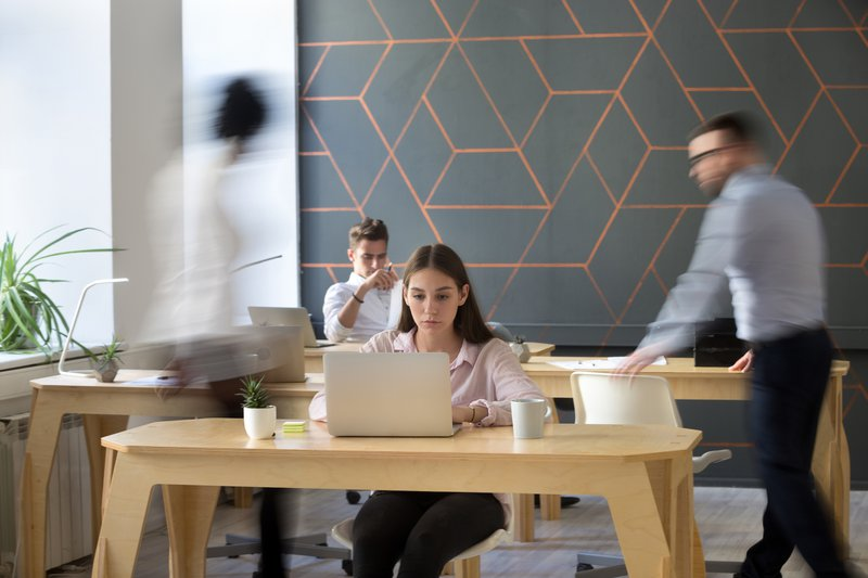 Office rush concept, corporate staff employees working together using computers at coworking, busy focused workers group walking in motion and sitting at desks in modern open space