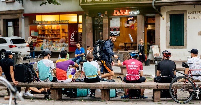 Strasbourg: Deliveroo, Foodora and Uber Eats employees resting near their bikes eating lunch in city center ready to deliver on time the food to the client.