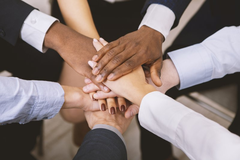 Business unity. Multiethnic corporate teame stacking hands together in office, close up