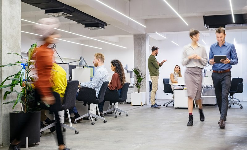 Group of businesswomen and businessmen working in modern office. Interior of busy coworking open space with staff walking and working together. Group of creative men and casual women working in creative agency.