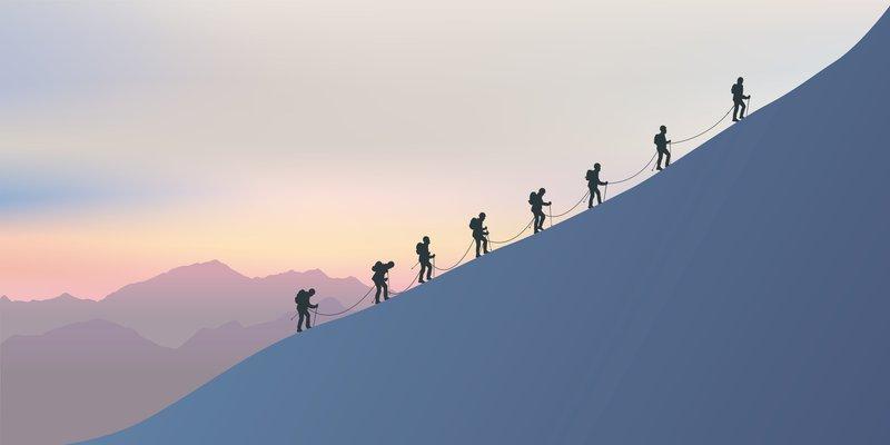 Une cordée d'alpinistes expérimentés escaladent le versant enneigé d'une montagne pour atteindre le sommet. A l'horizon le soleil se couche sur le paysage féérique.