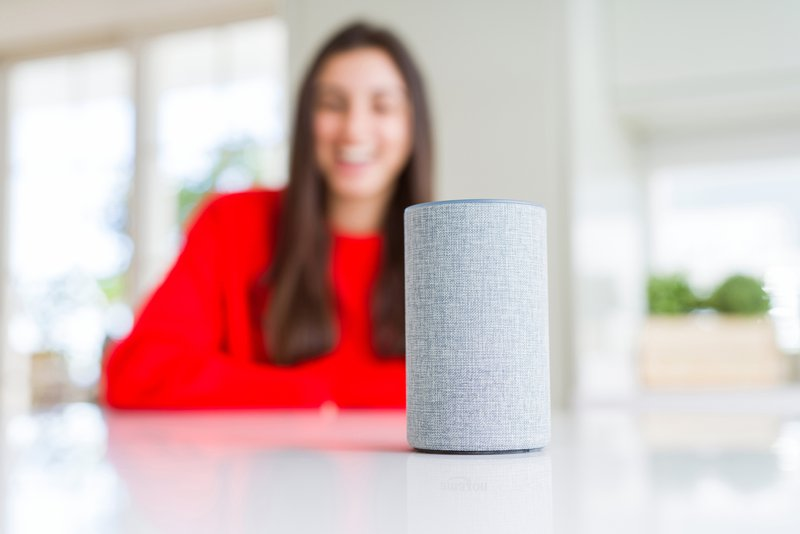 Young woman using home intelligent device, interactive voice assistant system