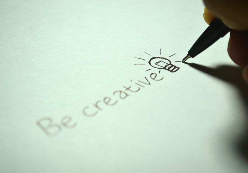 A pen writing the words 'be creative'