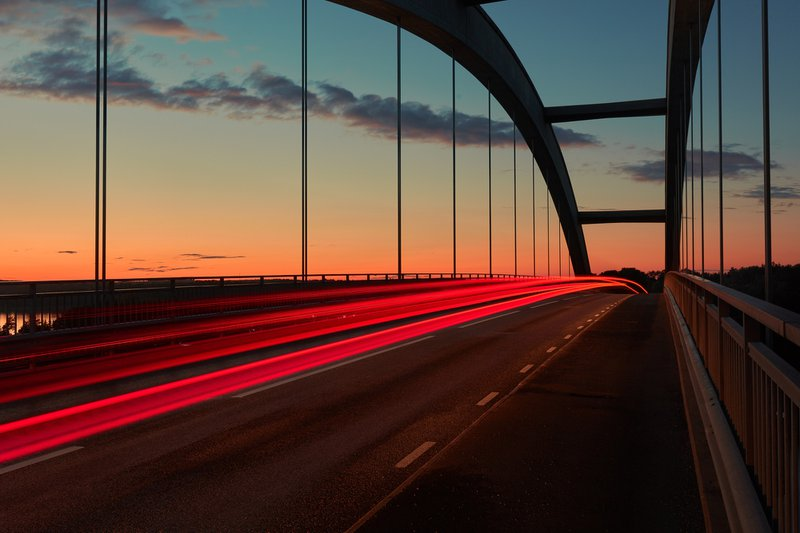 Sunrise light trail on a bridge