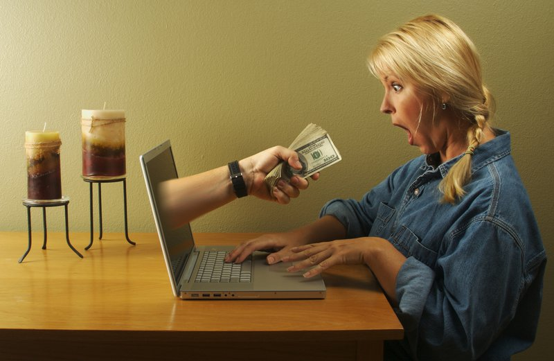 arm reaching through computer screen handing money to shocked woman