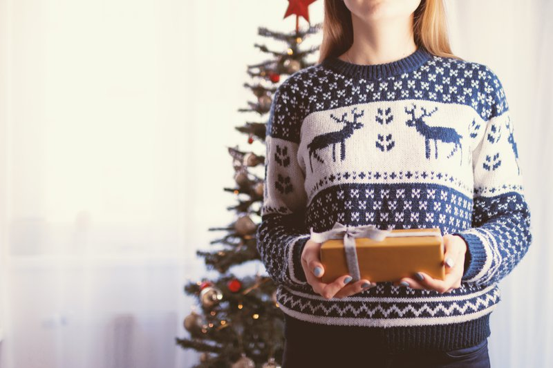 Dame draagt kersttrui en houdt een kerstcadeautje in haar handen
