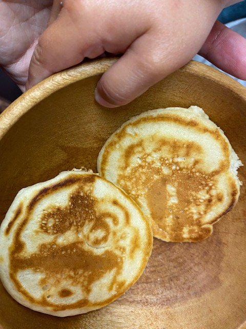 photo of toddler hand holding a wooden bowl that contains mini pancakes made with sourdough starter for lil helper blog