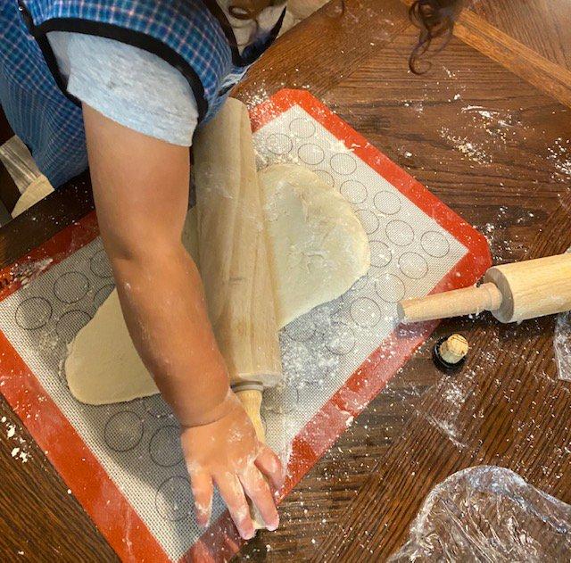 photo of toddler rolling dough for lil helper blog on sourdough starter