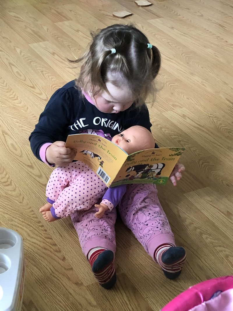 toddler reading to doll big sister new baby