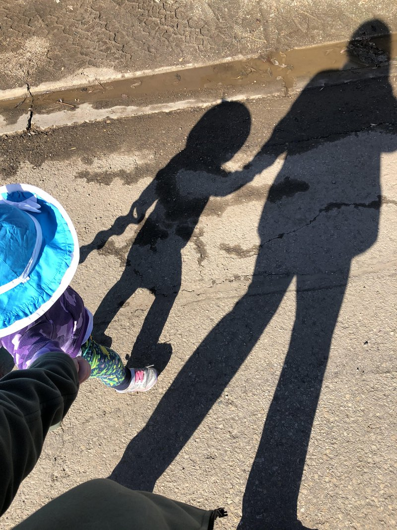 walk holding hands mom and toddler shadow