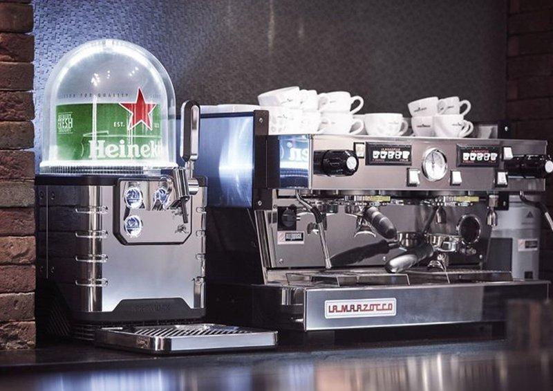 An Heineken Blade machine-result of Open Innovation- next to a coffee machine on a countertop