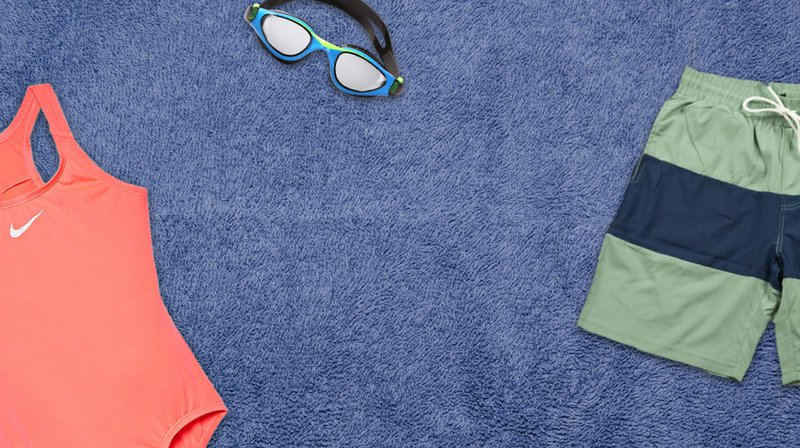 A women's swimsuit, pair of swimming trunks, and pair of goggles lay on a towel, viewed from overhead.