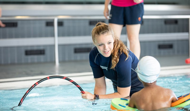 A woman is teaching swimming as a volunteer to get the experience required to become a lifeguard or swimming instructor.