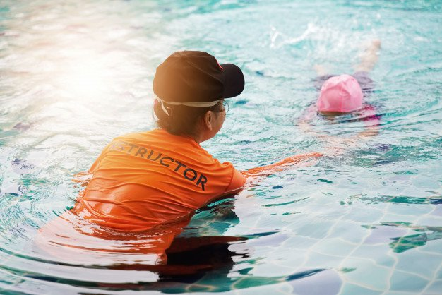A swimming instructor teaches a young student client to glide.