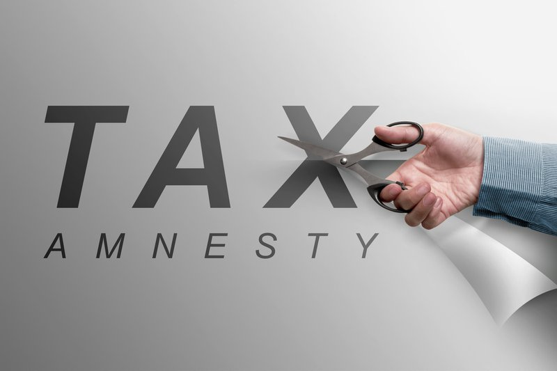 The hand cutting the paper that reads tax amnesty, business concept image