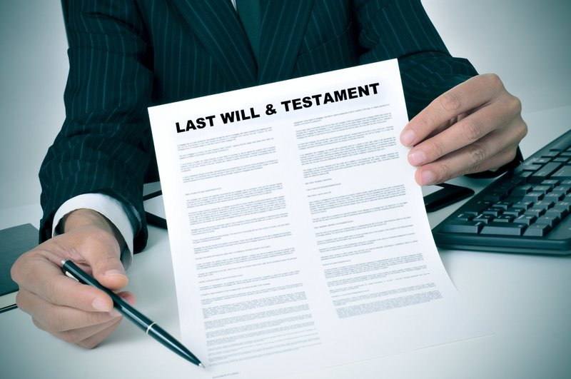 man in suit showing where the testator must sign in a last will and testament document