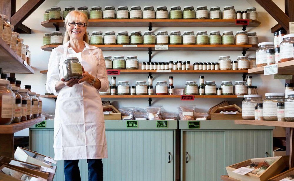 A small business retail store owner with cocoas and spices.