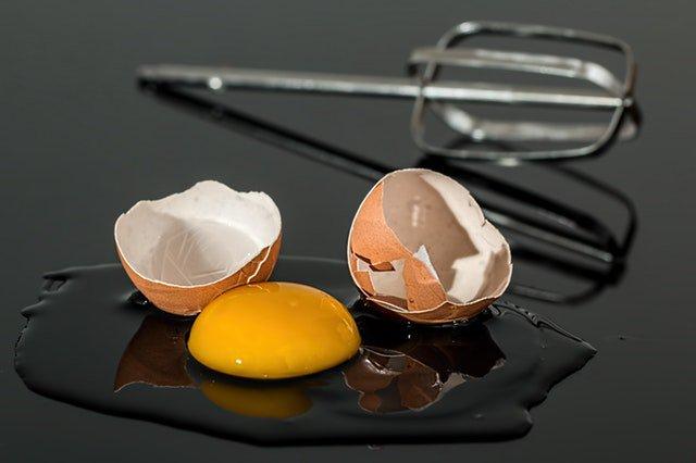 A broken egg next to a beater
