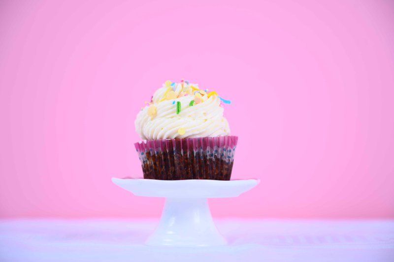 cupcake with sprinkles on ceramic pedestal