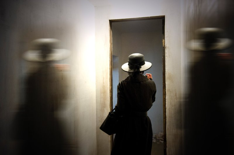 Mulher e suas sombras diante de uma porta