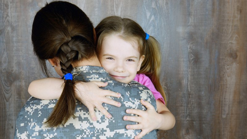 Cute little girl embracing soldier mother in uniform, armed forces duty parting