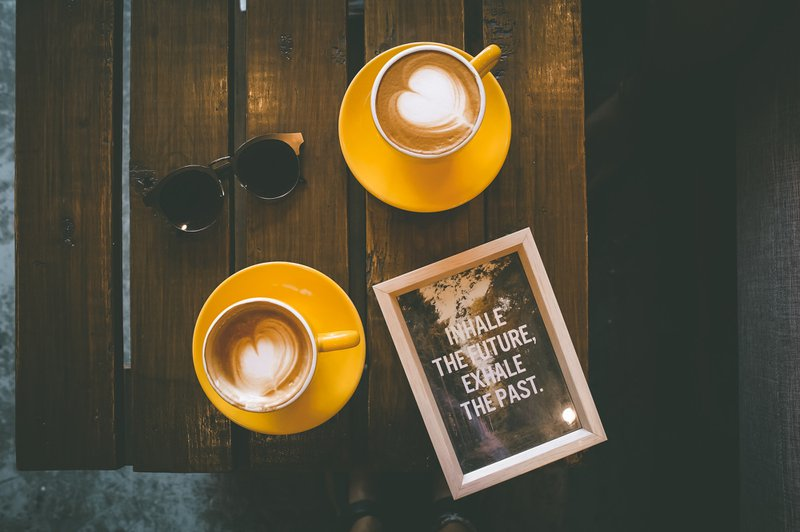 two coffee lattes in yellow cup with saucer on brown wooden table