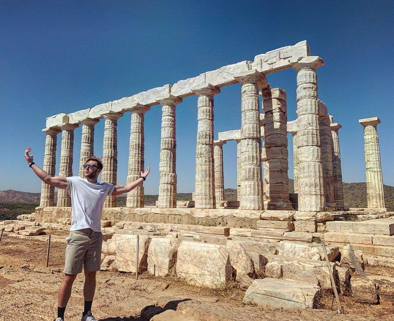 greek god pose while traveling through greece