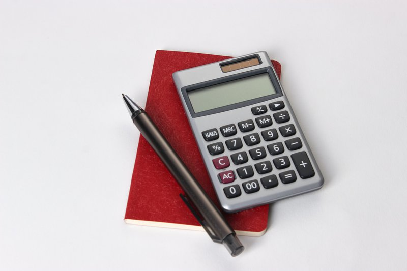 calculating equipment in the office using books, calculators and pens