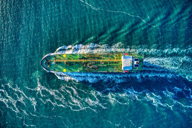 Green oil tanker headed out to sea aerial